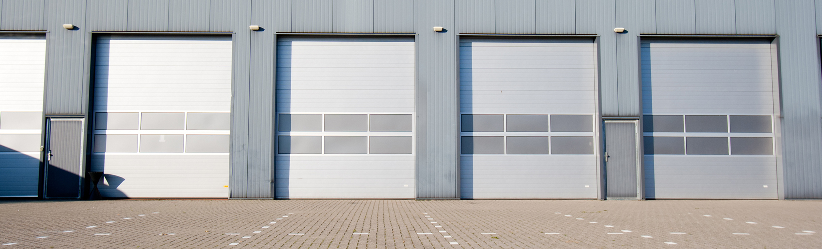 grey business building with four garage doors