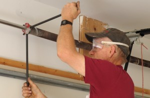 Man tightening a newly replaced garage door spring